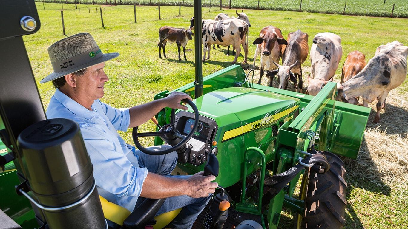 Trator Pequeno 5060E Série 5E com carregadora frontal alimentando o gado